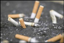A pile of used cigarettes that have been put out in an ash tray with black dirt