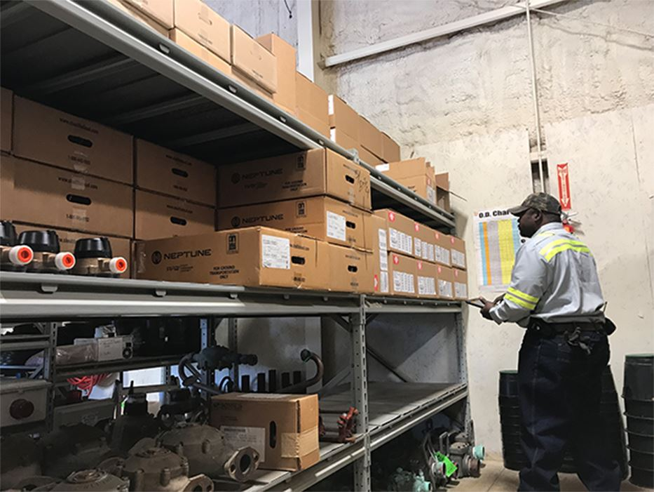 Utility Employee Looking at Boxes in a Warehouse