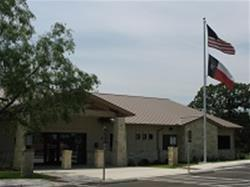 Front view of the Horseshoe Bay Police Department - Tan building with the American and Texas flags