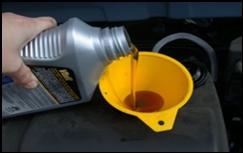 A bottle of oil being pouring into a car valve using a yellow funnel