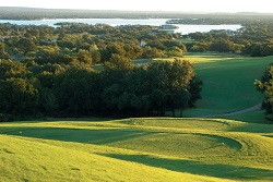 A lush, green golf course with trees along the water