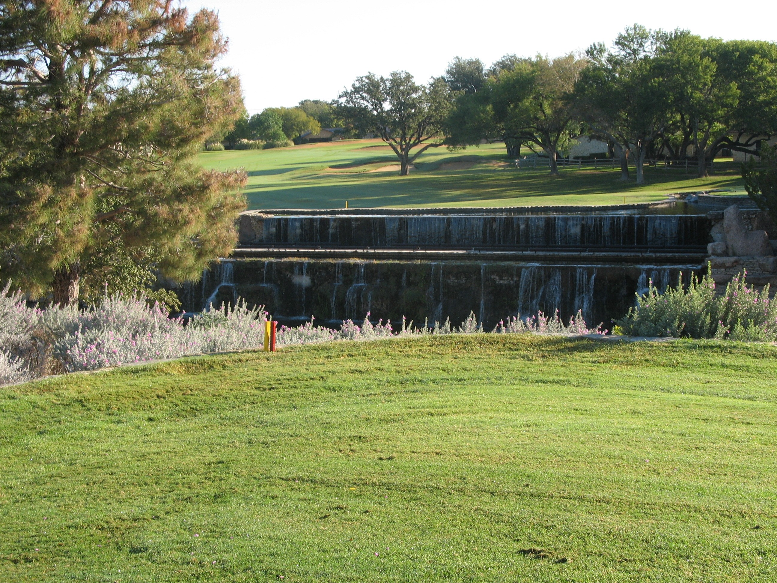 A golf course with a pond in the middle