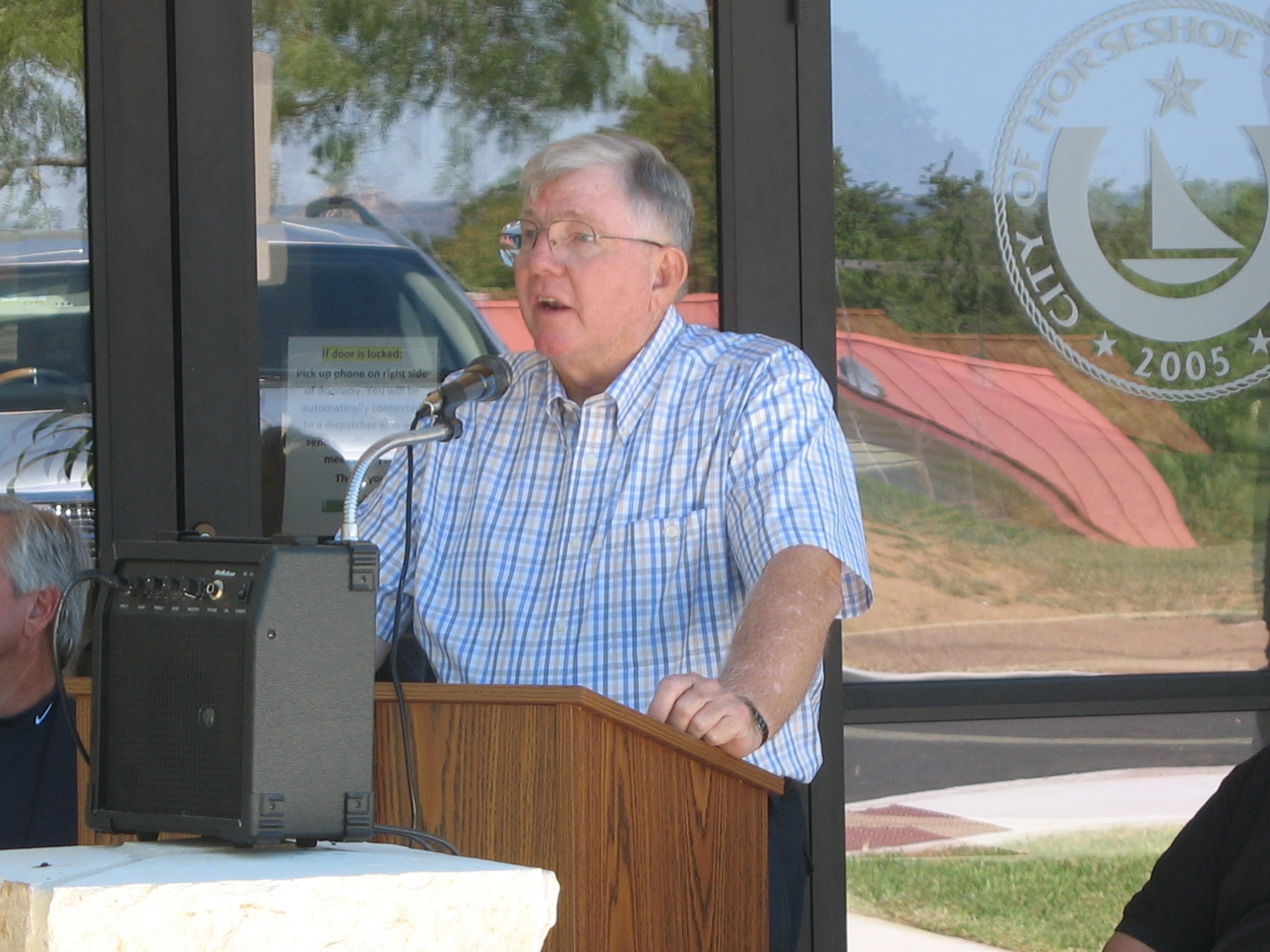 A man in a blue shirt speaking at a podium