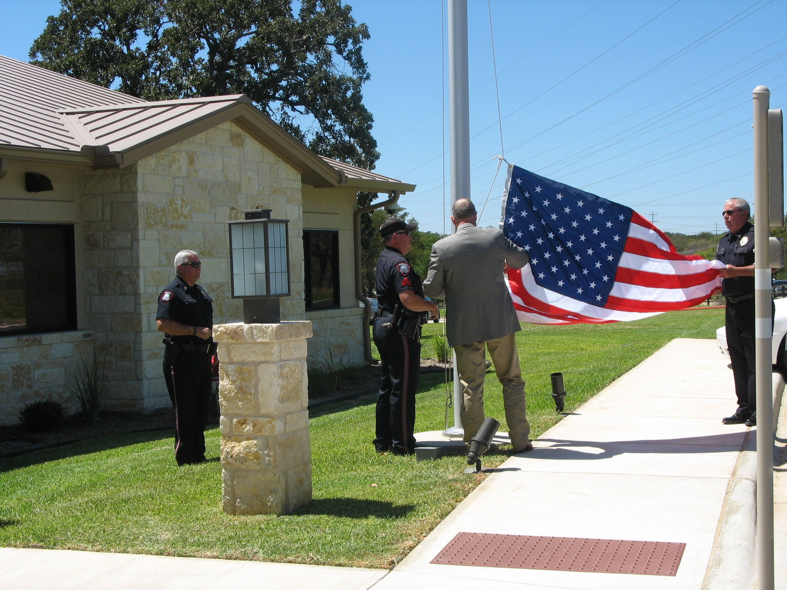 Officers and a man in a suit raising the American flag on a flag pole