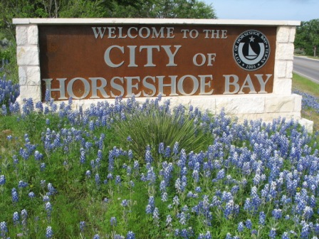 Welcome to the City of Horseshoe Bay sign with purple wildflowers in front of it