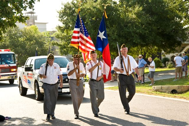 4 men holding flags walking in a parade