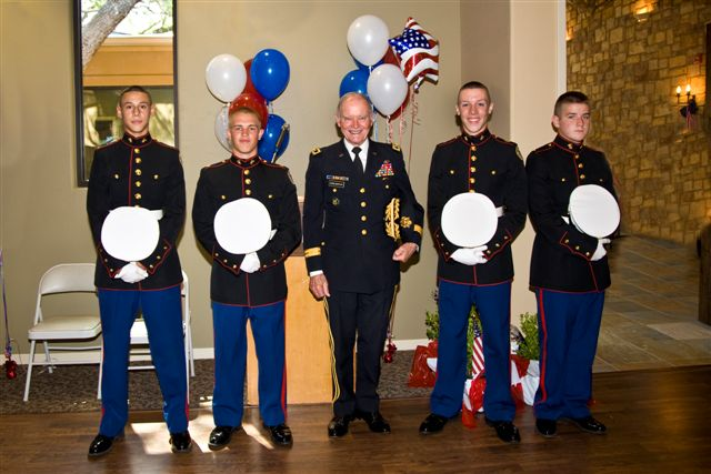 5 men in dress uniforms smiling for the camera with 4th of July balloons in the background