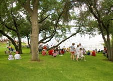 A crowd of people on the grass near the water watching a show on the 4th of July