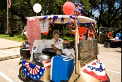 A woman in a golf cart decorated for the 4th of July