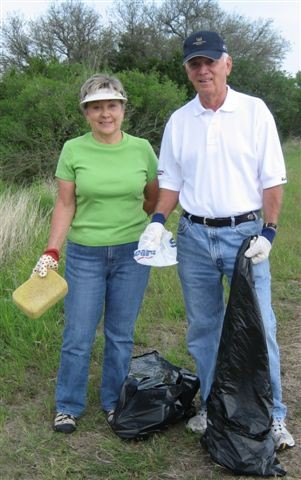 2 people with black trashbags smiling and cleaning up trash