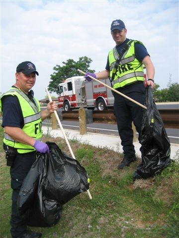 2 police officers in green safety vests cleaning up trash on the side of the road