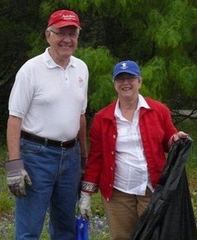 A man and a woman with a trash bag cleaning up the forest