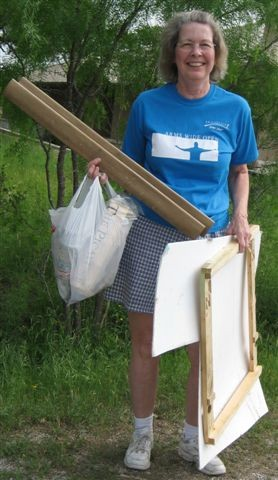 A woman in a blue shirt holding supplies outside