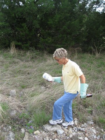 A woman with gloves on cleaning up trash in the meadow